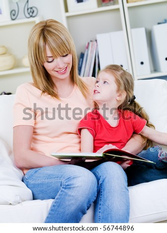Portrait of young happy  mother studing her little daughter to read - at home - stock photo