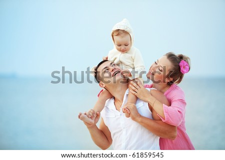 Portrait of young happy parents with child at the beach - stock photo