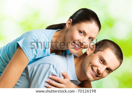 Portrait of young happy smiling amorous couple, outdoors - stock photo