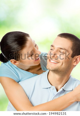Portrait of young happy smiling attractive amorous couple, outdoors, with copyspace area - stock photo