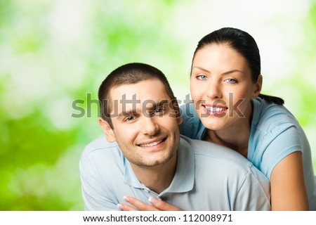 Portrait of young happy smiling attractive couple, outdoors - stock photo