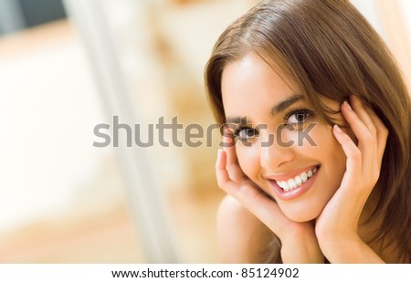 Portrait of young happy smiling beautiful woman, at home. You can use left part as copyspase for slogan or text. - stock photo