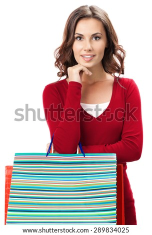 Portrait of young happy smiling brunette woman in red casual clothing with shopping bags, isolated on white background - stock photo