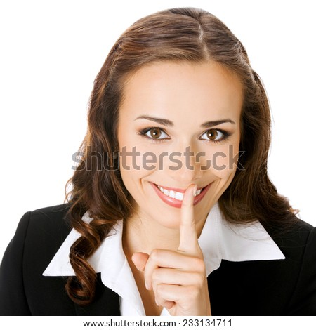 Portrait of young happy smiling business woman keeping finger on her lips and asking to keep quiet, isolated against white background - stock photo