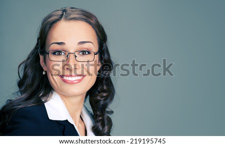 Portrait of young happy smiling business woman, over gray background, with copyspace - stock photo