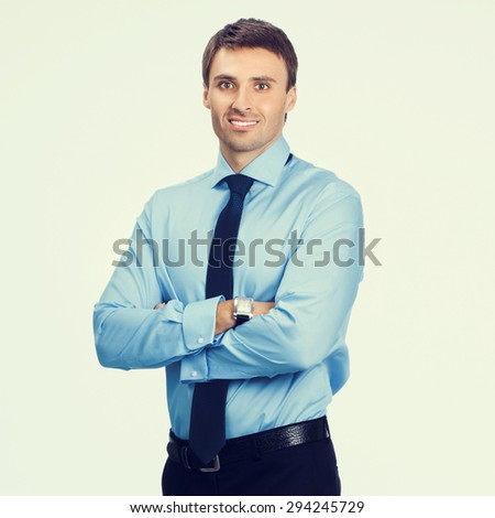 Portrait of young happy smiling businessman, in blue confident business wear - stock photo