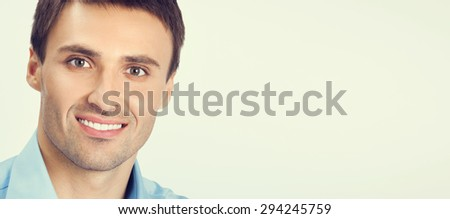 Portrait of young happy smiling businessman in blue confident business wear, with blank copyspace area for slogan or text message