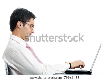 Portrait of young happy smiling businessman in glasses working with laptop, isolated on white background