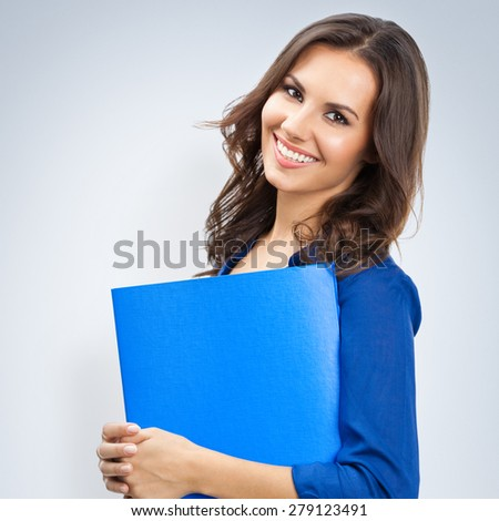 Portrait of young happy smiling businesswoman with blue folder, with blank copyspace area for slogan or text - stock photo