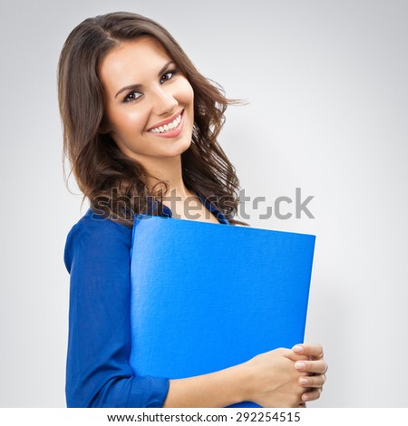 Portrait of young happy smiling businesswoman with blue folder, with blank copyspace area for slogan or text, posing at studio against grey background - stock photo