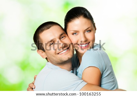 Portrait of young happy smiling cheerful attractive amorous couple, outdoors - stock photo