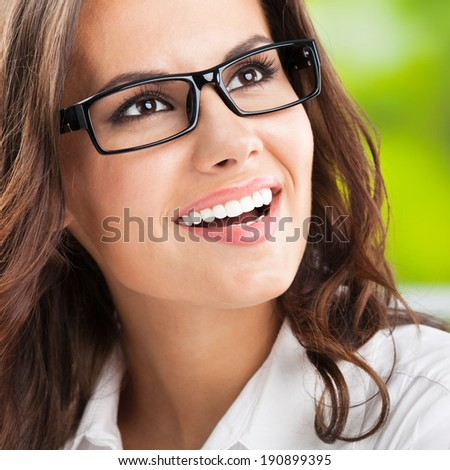 Portrait of young happy smiling cheerful business woman at office, with copyspace