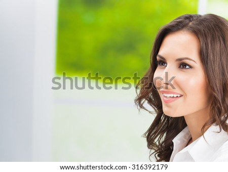 Portrait of young happy smiling cheerful business woman at office, with copyspace - stock photo