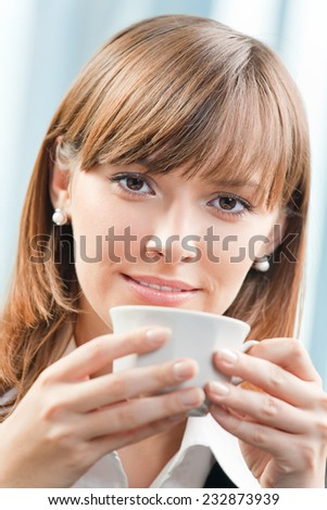 Portrait of young happy smiling cheerful businesswoman with cup of coffee at office - stock photo