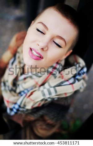 Portrait of young happy smiling girls with very short hair and closed eyes wearing a scarf and coat. City lifestyle.