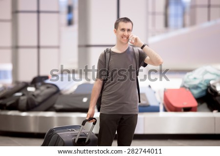 Portrait of young happy smiling handsome traveller man in 20s leaving arrivals lounge of airport terminal building after collecting his baggage at conveyor belt, talking on cellphone - stock photo