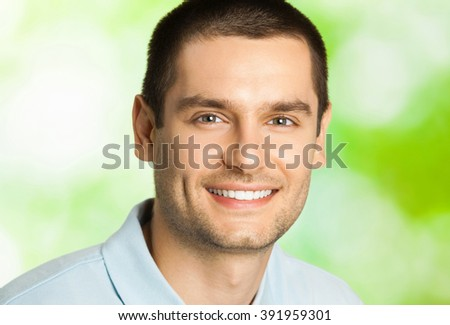 Portrait of young happy smiling man with plate of salad, outdoors - stock photo