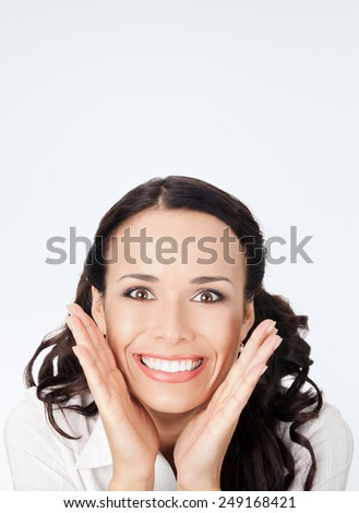 Portrait of young happy smiling surprised business woman, against grey background, with copyspace - stock photo