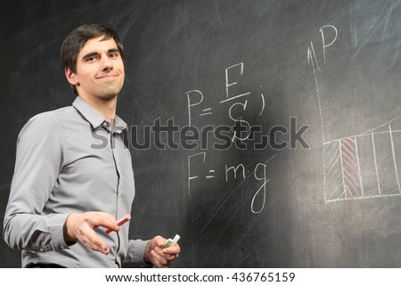 Portrait of young happy smiling teacher man standing near chalkboard with mathematical formulas and speaking to audience