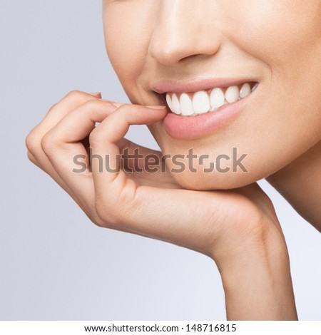 Portrait of young happy smiling thinking woman, over grey background