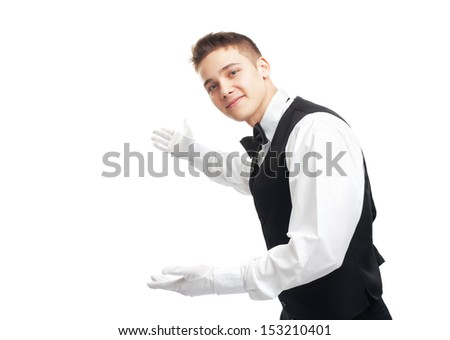 Portrait of young happy smiling waiter gesturing welcome isolated on white background
