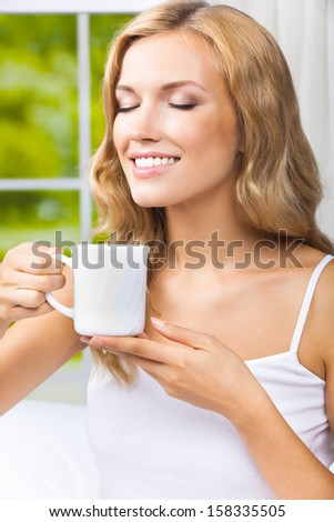 Portrait of young happy smiling woman drinking coffee or tea, at home