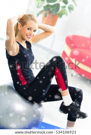 Portrait of young happy smiling woman in sportswear, doing fitness exercise with fit ball, indoors. Healthy lifestyle, weight lossing and sporting theme concept shot. Over snow.