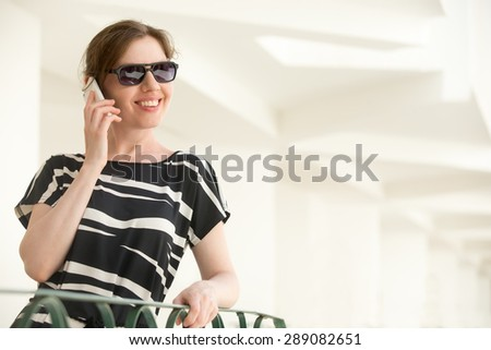 Portrait of young happy smiling woman in sunglasses and black and white summer dress standing in a building with white stucco walls, talking on cellphone, making call, copy space - stock photo