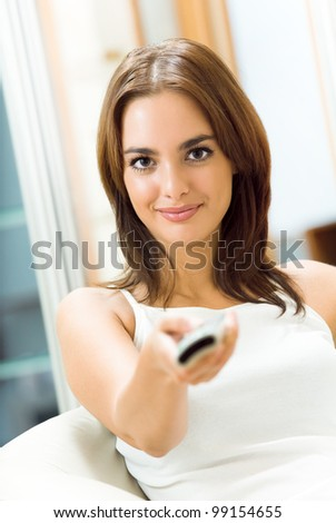 Portrait of young happy smiling woman watching TV at home - stock photo