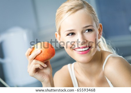 Portrait of young happy smiling woman with apple at home - stock photo