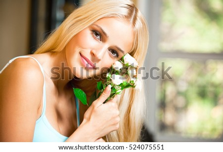 Portrait of young happy smiling woman with bouquet of white roses. Caucasian blond model in home leisure and happiness concept.