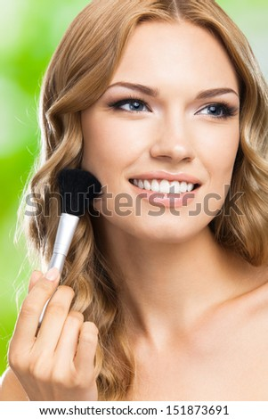 Portrait of young happy smiling woman with make up brush, outdoors