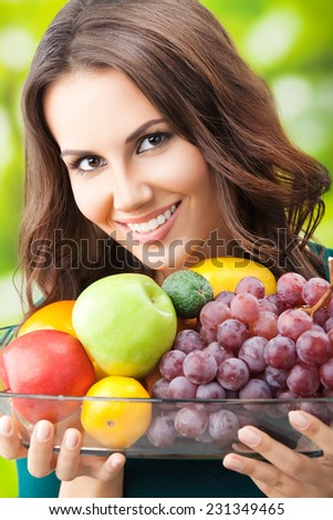 Portrait of young happy smiling woman with plate of fruits, outdoor