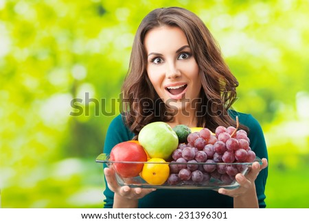 Portrait of young happy smiling woman with plate of fruits, outdoor, with copyspace  - stock photo