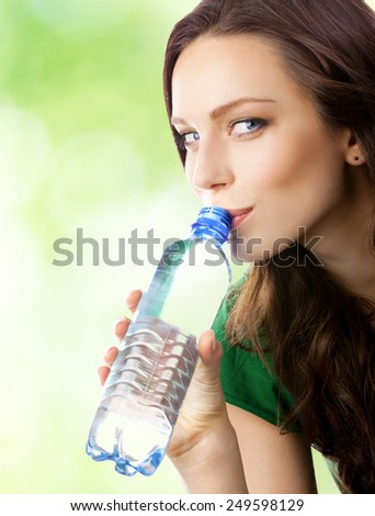 Portrait of young happy woman drinking water from bottle, outdoor - stock photo
