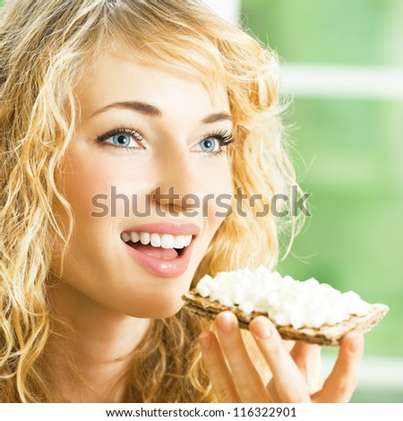 Portrait of young happy woman eating crispbread with cheese - stock photo