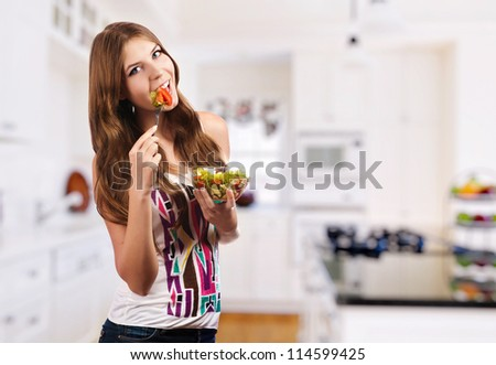 Portrait of young happy woman eating salad at kitchen - stock photo