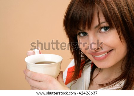 Portrait of young happy woman holding cup with tea on brown background - stock photo