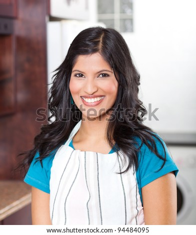 portrait of young happy woman in apron in kitchen