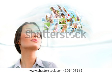 Portrait of young happy woman looking at photo and video files of her family in social media resources. Indoors at office - stock photo