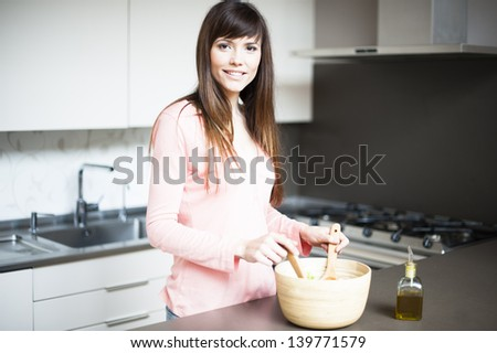 Portrait of young happy woman making salad at domestic kitchen - stock photo