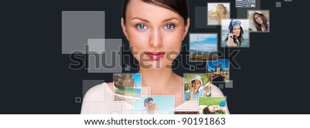Portrait of young happy woman sharing his photo and video files in social media resources. Studio shot against gray background - stock photo