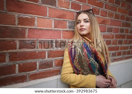 Portrait of young happy woman standing by the brick wall