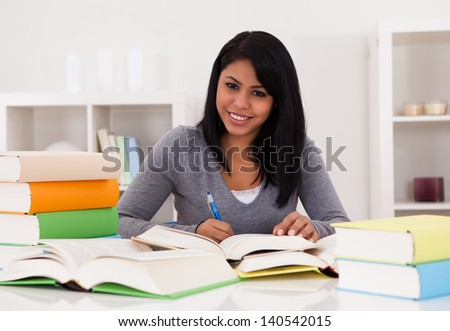 Portrait Of Young Happy Woman Studying At Home - stock photo