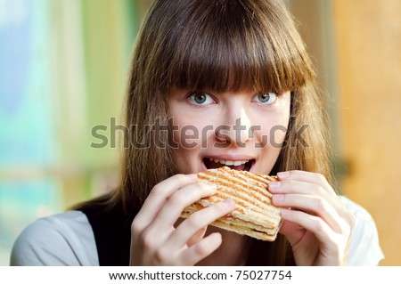 Portrait of young happy woman with sandwich at cafe - stock photo
