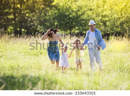 Portrait of young happy ypung family walking in sunny meadow