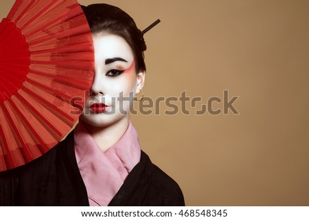 Portrait of young heisha in kimono hiding the half of her face behind the red handheld fan.  Studio shot. Copy space.