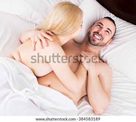 Portrait of young heterosexual pair making love in bedroom - stock photo