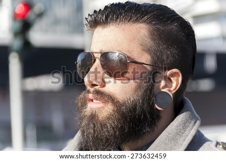 portrait of young hipster businessman in the heart of city - stock photo