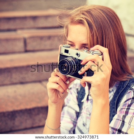 Portrait of young hipster girl making photo with vintage camera. Modern youth lifestyle concept. Lovely face. Photo toned style instagram filters - stock photo